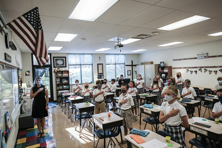 Fourth-grade teacher Kristina Tons, wearing a clear plastic face shield, leads her class in the Pledge of Allegiance.