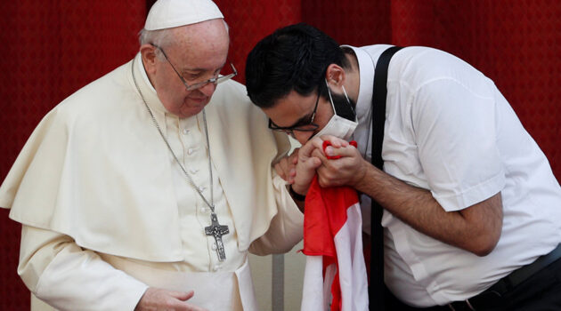 A masked Maronite Father Georges Briedi kisses the hand of Pope Francis