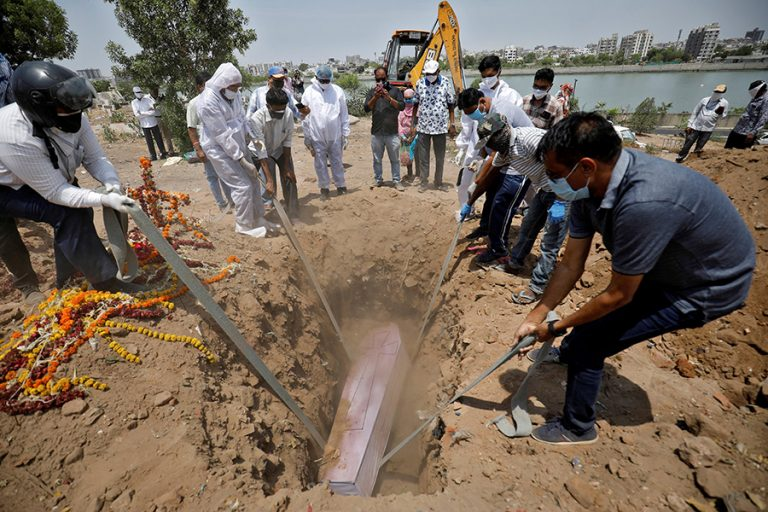 People lower the body of a man who died of COVID-19 into a grave at a cemetery in Ahmedabad, India.